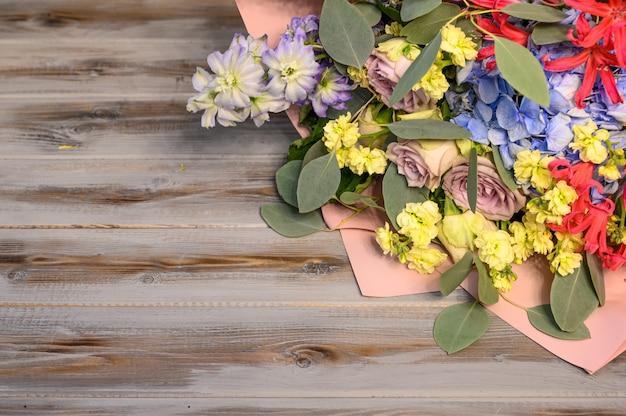木製の背景にバラや他の花の花束