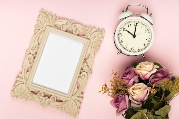 時計とフレームの横にあるバラの花束