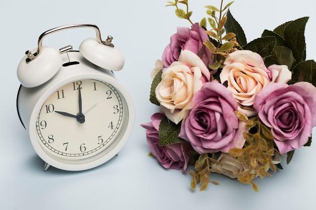 時計の横にあるバラの花束