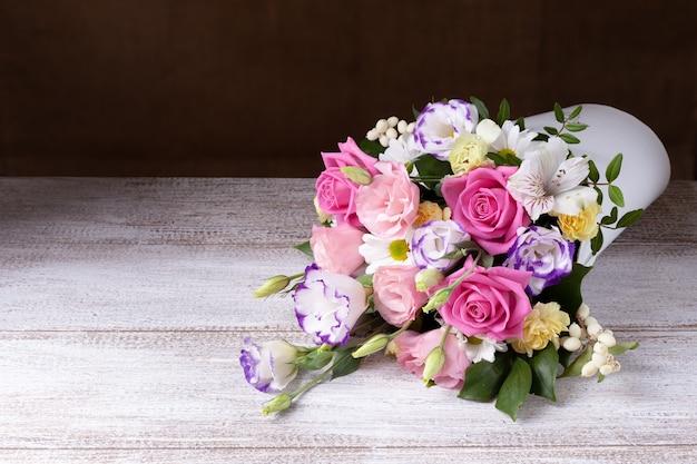 Букет из роз, ромашек, лизиантусов, хризантем, неоткрытых бутонов в белой круглой коробке.