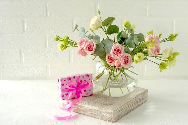 愛の贈り物の横にあるテーブルの上のガラスのスタイリッシュな花瓶にバラ、トルコギキョウ、ユーカリの花束。室内装飾用の花の構成。