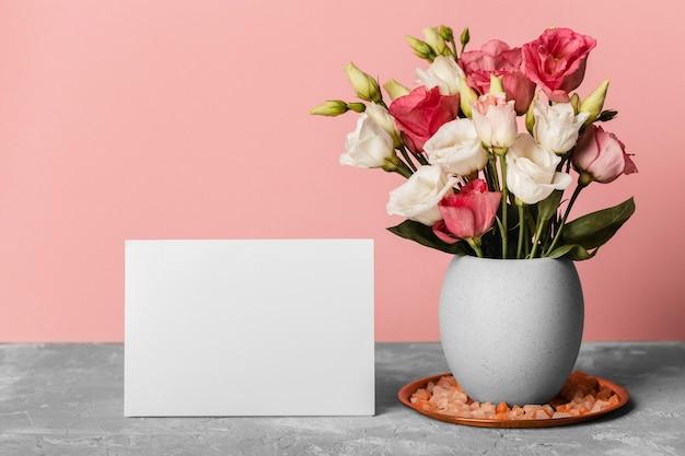 空白のカードの横にある花瓶のバラの花束
