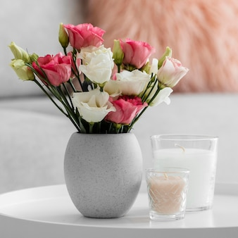 촛불 옆 꽃병에 장미 꽃다발