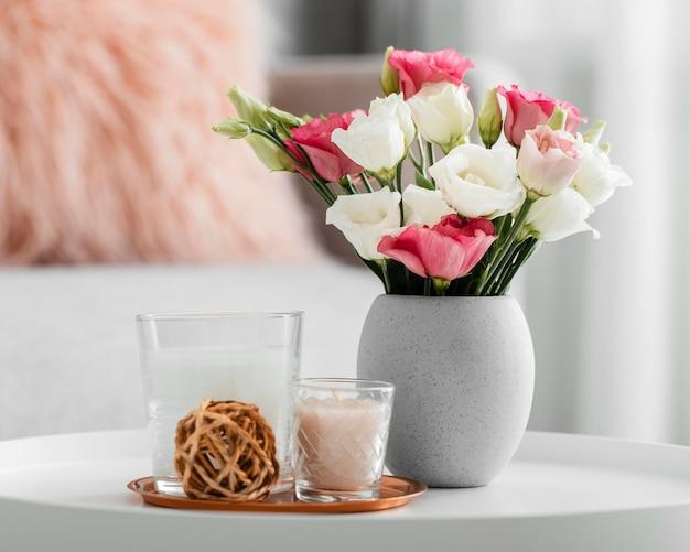장식 개체 옆에있는 꽃병에 장미 꽃다발