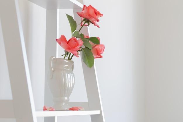 白い背景の上の花瓶にバラの花束