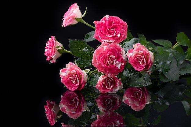Букет роз на черной поверхности с отражениями цветов от блестящей поверхности.