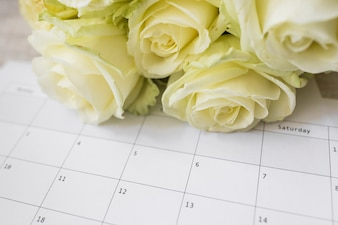 Bouquet of roses on calendar with dates