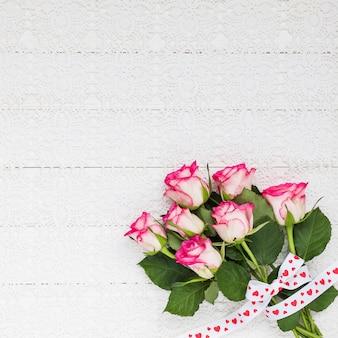 白いかぎ針編みのテーブルクロスにバラの花束。上面図