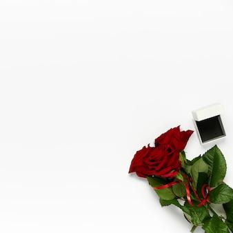 白い背景の上のリングのボックスとバラの花束。聖バレンタインテンプレート、フラットレイ、上面図