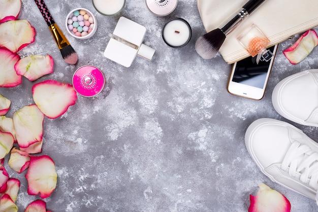 Букет из роз с косметикой в парфюмерии, телефоне и кроссовках на сером фоне
