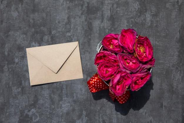 白い封筒とバラの花束