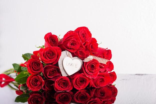 Букет роз с деревянными сердечками. макет поздравительной открытки.