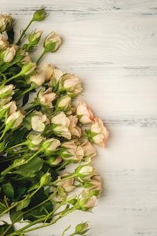 Букет из маленьких светло-розовых роз на белом деревянном столе, копия пространства