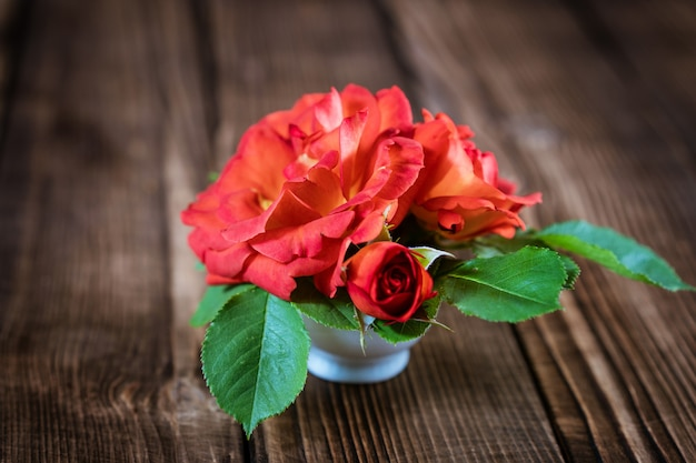 나무 바닥에 꽃병에 작은 빨간 장미 꽃다발
