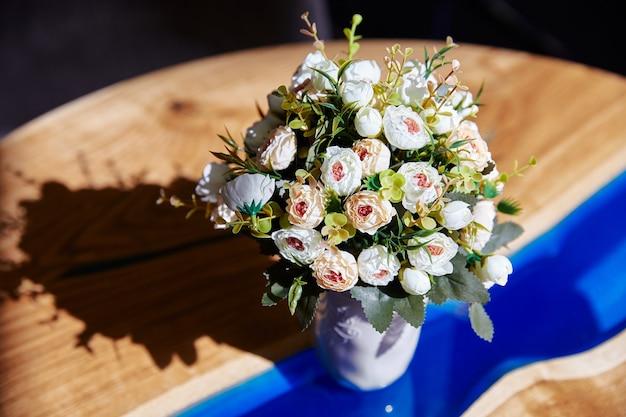 На столе букет маленьких роз в вазе