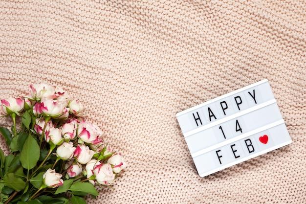 ほこりっぽいピンクの毛布に小さなバラの花束、バレンタインデーを意味するハッピー14febの碑文が付いたライトボックス。 Premium写真