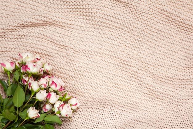 ほこりっぽいピンクの毛布に小さなバラの花束。
