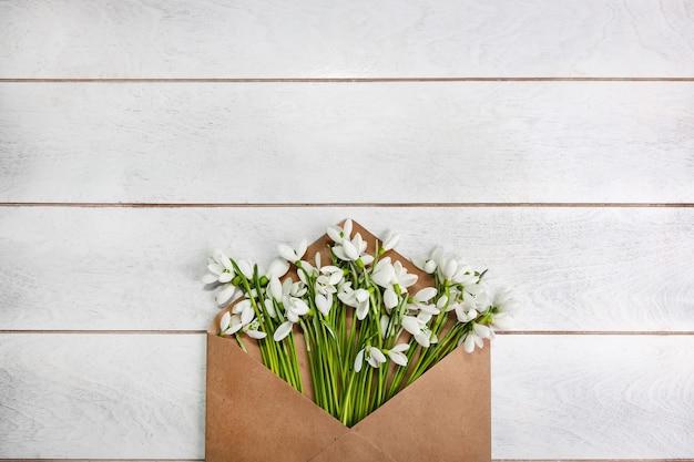 Букет подснежников galanthus nivalis лежит в крафтовом конверте на светлой деревянной поверхности.