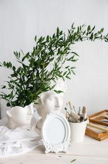 スカンジナビアのインテリアのモックアップフレームとモダンなセラミック花瓶のスノードロップの花束