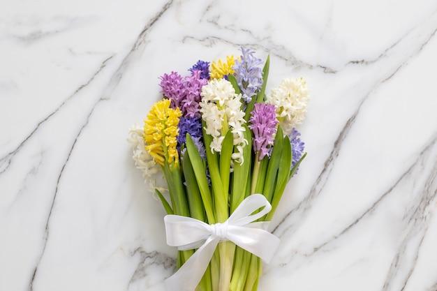 Букет весенних разноцветных цветов гиацинтов белый мрамор