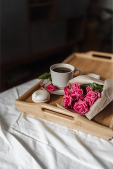 ベッドの木製トレイに春の花とコーヒーの花束の花束