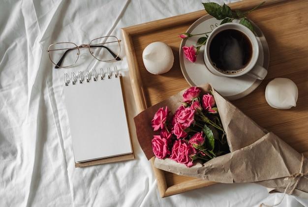 봄 꽃의 꽃다발과 침대에서 나무 쟁반에 커피 한 잔