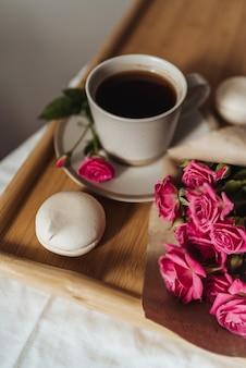 Букет весенних цветов и чашка кофе на деревянном подносе в постели