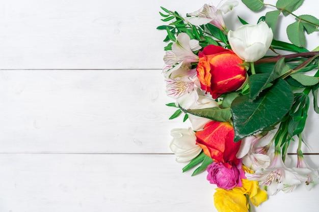 텍스트에 대 한 장소를 가진 흰색 나무 배경에 봄 꽃의 꽃다발. 복사 공간으로 조롱 프리미엄 사진