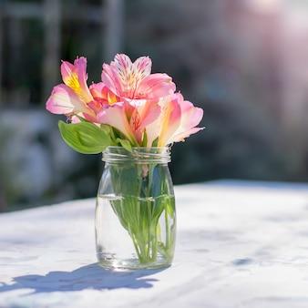 カフェのテーブルに春のピンクの花のクローズアップの花束