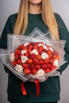 여자의 손에 딸기와 장미 꽃다발.
