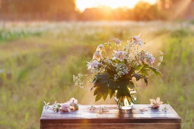 야외 햇빛에 유리 꽃병에 여름 꽃의 꽃다발
