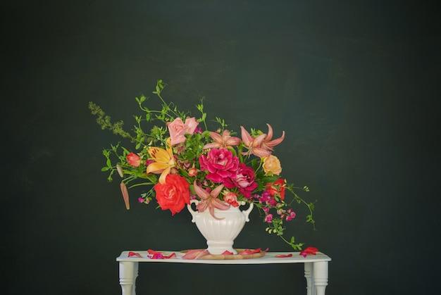 어두운 배경에 빈티지 화이트 나무 선반에 꽃병에 여름 꽃의 꽃다발