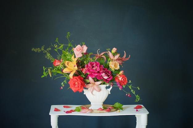 어두운 벽에 빈티지 화이트 나무 선반에 꽃병에 여름 꽃의 꽃다발