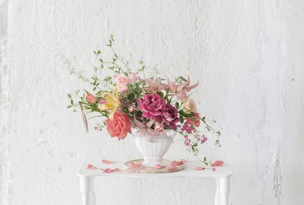 흰색 바탕에 빈티지 화이트 나무 선반에 꽃병에 여름 꽃의 꽃다발
