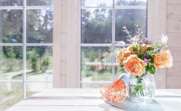 窓の近くのガラスの花瓶に夏のバラの花束