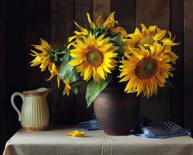 나무 배경 테이블에 찰 흙 주전자에 해바라기의 꽃다발.