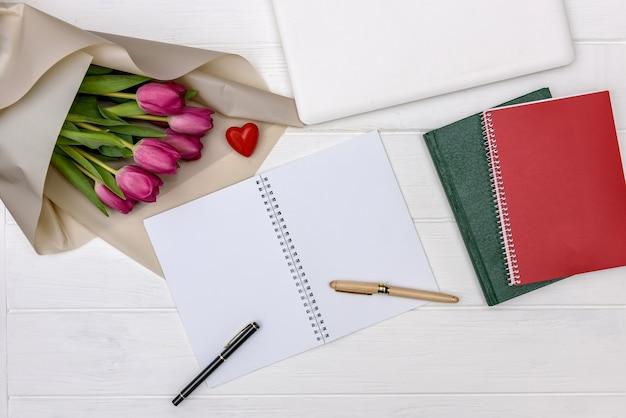 Букет тюльпанов и пустой блокнот на деревянном столе