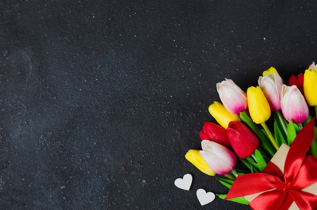 チューリップと暗い背景にギフトボックスの花束。バレンタインデー、女性の日、母の日のグリーティングカード。