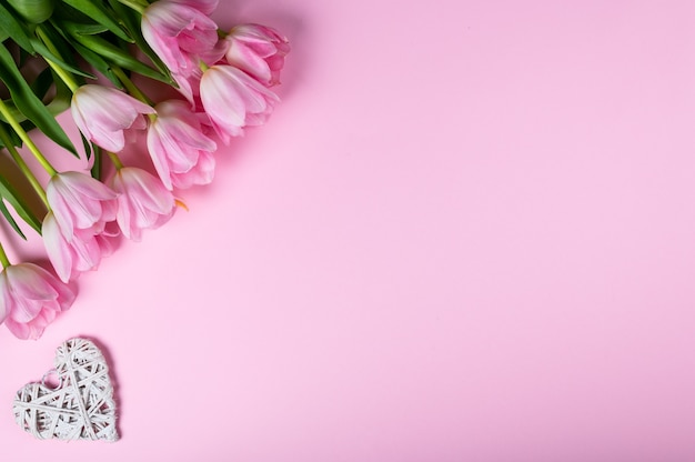 ピンクの背景にチューリップとハートの花束。上面図、フラットレイスタイル。