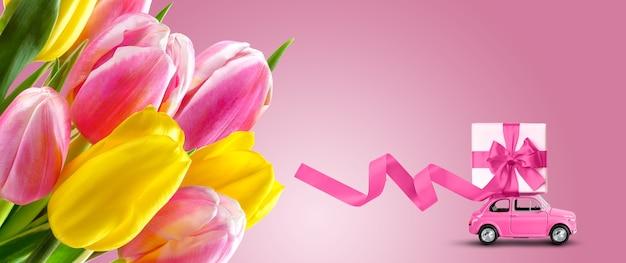 ピンクの背景の屋根にギフトボックスとチューリップとピンクのおもちゃの車の花束。グリーティングカード、バナーデザインテンプレート