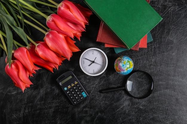 Букет тюльпанов и школьных принадлежностей на доске. знания, день учителя, снова в школу