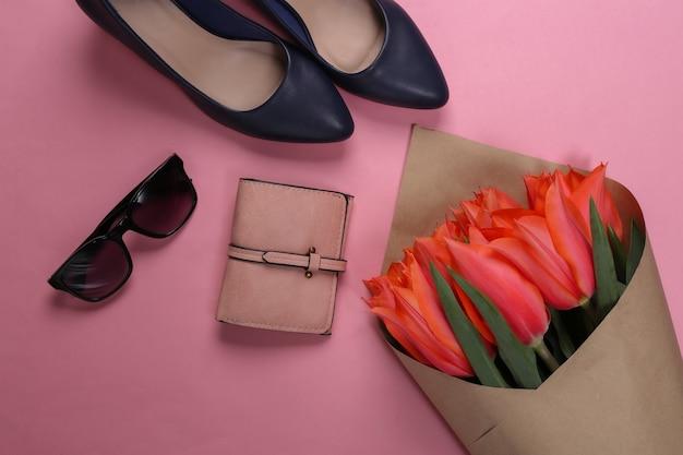 ピンクのパステルカラーの背景にチューリップとレディースアクセサリーの花束。休日の母の日または3月8日、誕生日。上面図