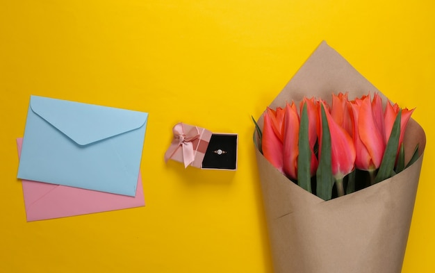 Букет тюльпанов, золотое кольцо с бриллиантом в подарочной коробке, конверты с буквами на желтом.
