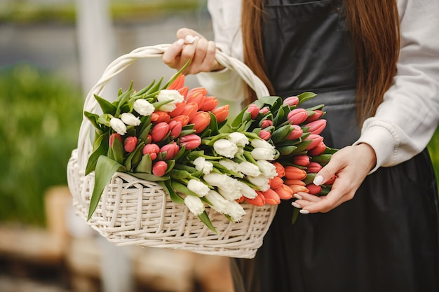 Букет тюльпанов в парне. парень и девушка в оранжерее. г. садовники в фартуках.