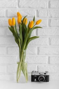 카메라와 함께 투명 꽃병에 튤립 꽃다발