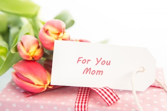 Bouquet of tulips next to a gift with a card for a mother
