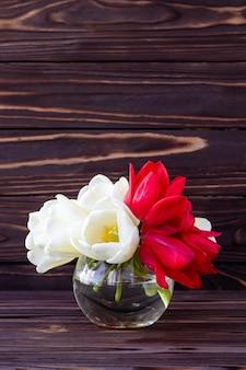 Букет из тюльпанов на деревянный стол. праздничная подарочная карта, праздничная рамка. место для текста.