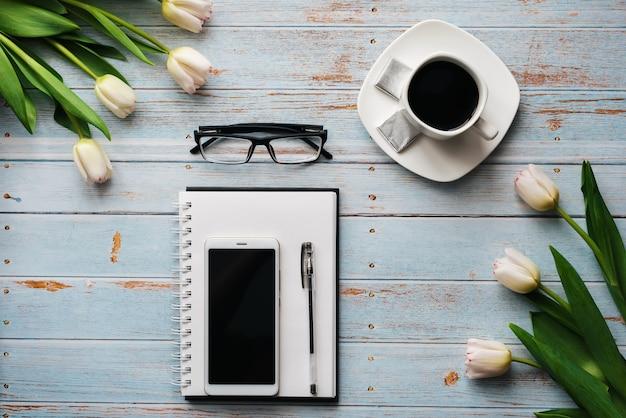 空のノートブック、一杯のコーヒー、木製の背景にスマートフォンとチューリップの花束