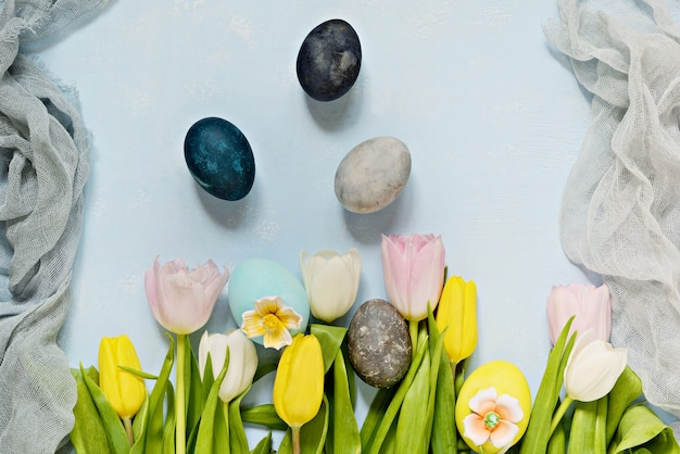 水色の背景にイースターエッグとチューリップの花束