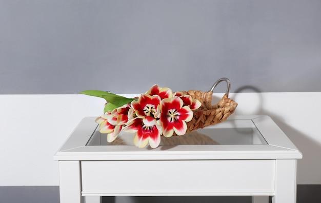 縞模様の壁の近くの白いテーブルの上の多彩なチューリップの花束